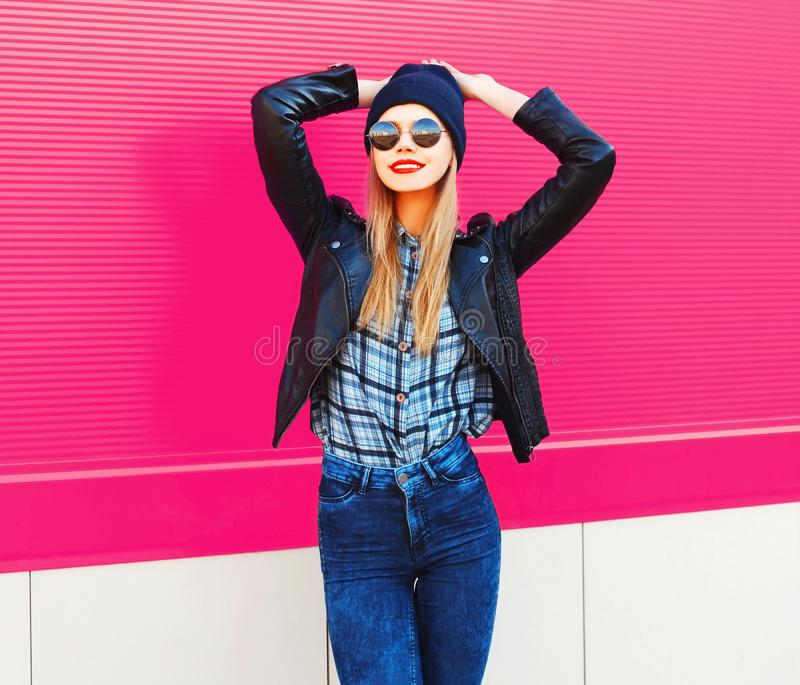 portrait stylish happy smiling woman in rock black style jacket, hat posing on city street over colorful pink wall stock photography