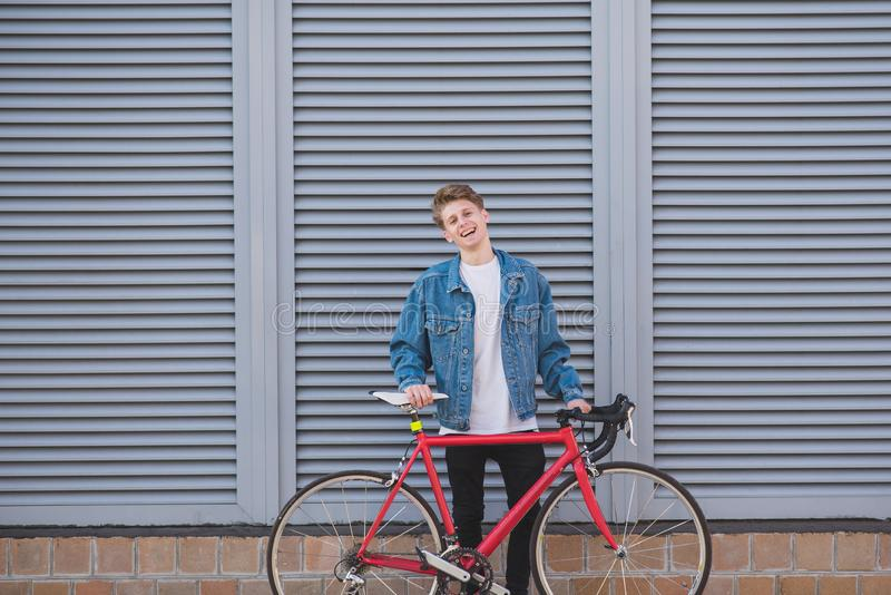 Portrait of a stylish, happy young man in a denim jacket and a red bicycle on the background of a gray wall royalty free stock photography