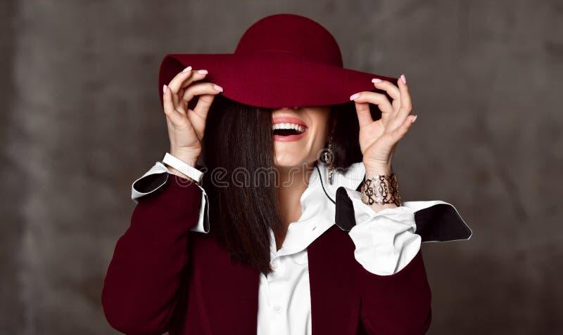 Portrait of stylish high-society lady in black jacket and white shirt pulling down hat brim hiding her eyes and laughs. Portrait of stylish high-society lady stock photos