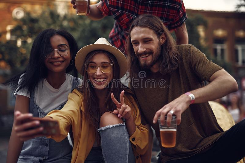 Cheerful young people making selfie while spending time outdoors stock photo