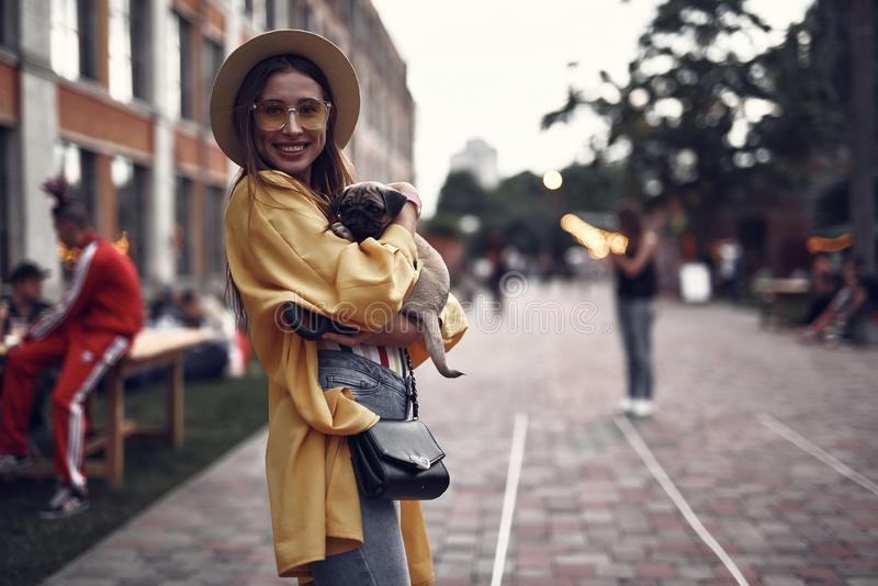 Cheerful young lady with little dog standing on the street stock photography