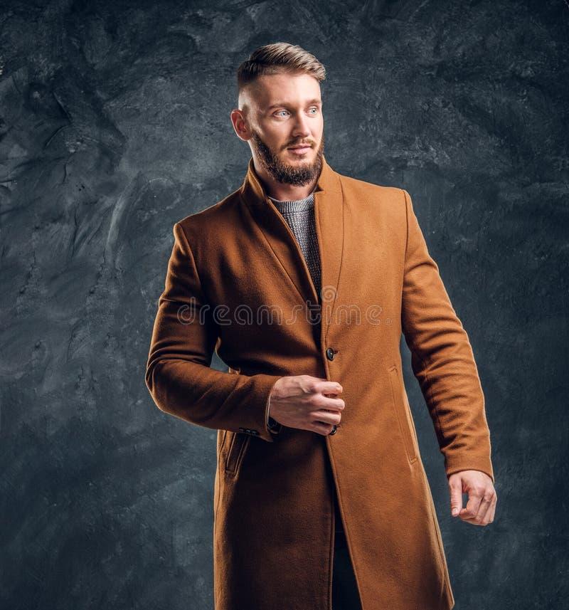 Portrait of a stylish male wearing the demi-season coat. Men`s beauty, seasonal fashion. Studio photo against a dark stock photos