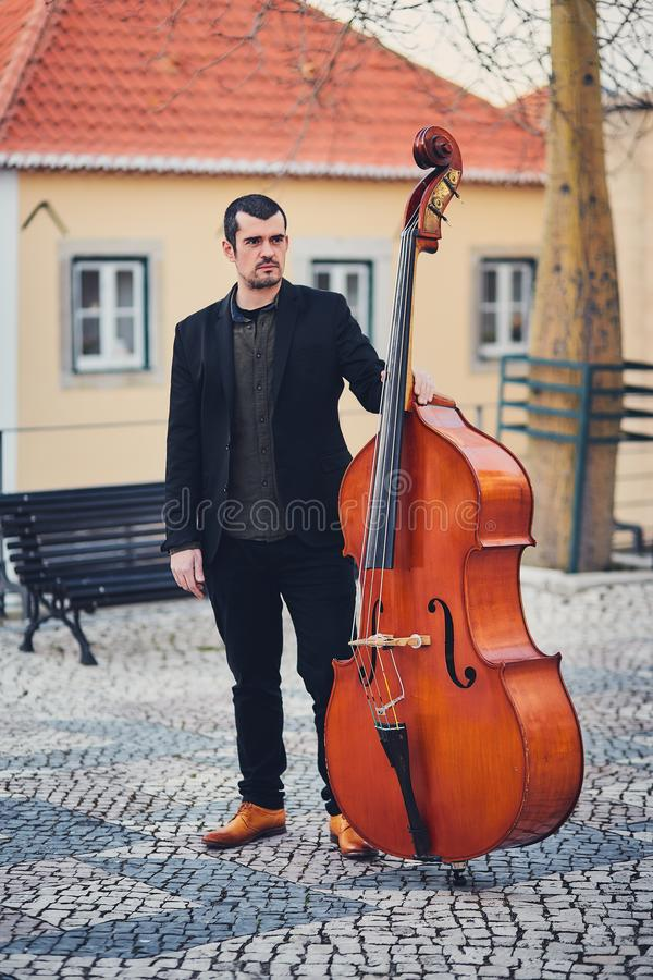 Portrait of a stylish man with a beard on an old street with a double bass. A solid musician with a large musical instrument in br stock photography