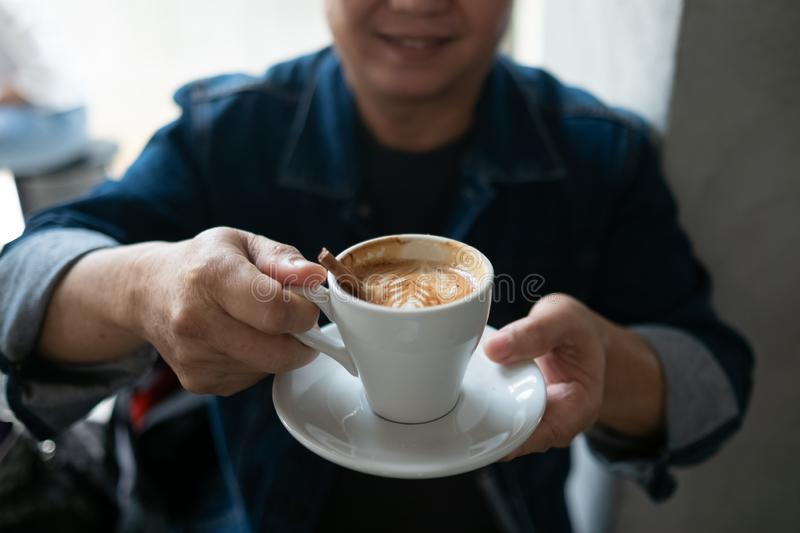 Portrait of stylish young man with cup of coffee.. Cappuchino or latte coffe in a white cup on a dark background. Portrait of stylish man with cup of coffee stock photography