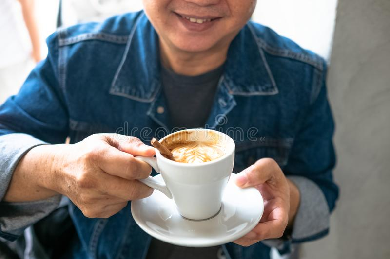 Portrait of stylish young man with cup of coffee.. Cappuchino or latte coffe in a white cup on a dark background. Portrait of stylish man with cup of coffee stock photo