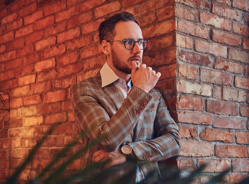 Portrait of a stylish man in a flannel suit and glasses leaning against a brick wall in a room with loft interior. stock photography