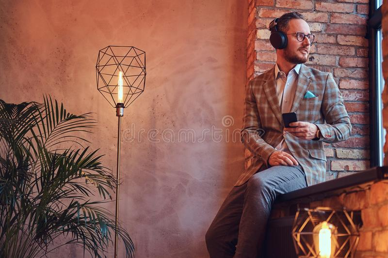 Portrait of a stylish man in a flannel suit and glasses listening music with the phone and headphones sitting on a royalty free stock photo