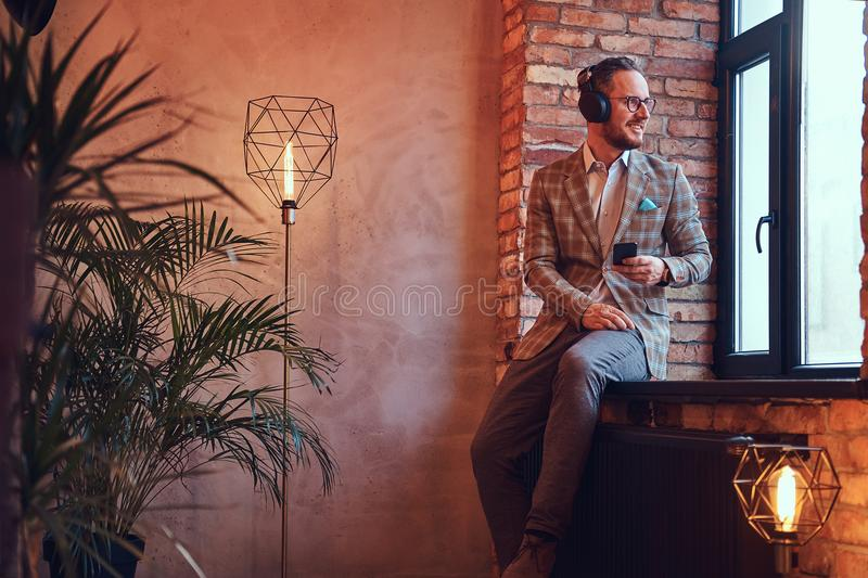 Portrait of a stylish man in a flannel suit and glasses listening music with the phone and headphones sitting on a royalty free stock images