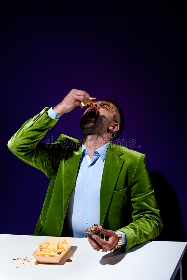 Portrait of stylish man in green velvet jacket eating french fries with ketchup at table. With blue background stock photos