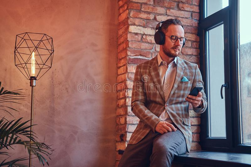 Portrait of a stylish man in a flannel suit and glasses listening music with the phone and headphones sitting on a stock image