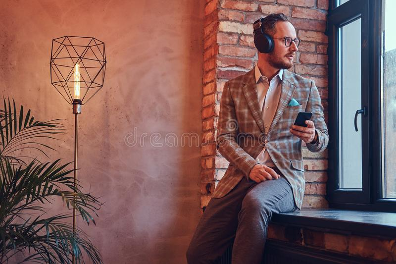 Portrait of a stylish man in a flannel suit and glasses listening music with the phone and headphones sitting on a stock photography