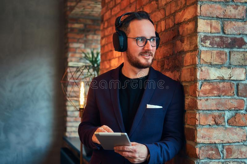 Portrait of a handsome bearded male wearing stylish suit listening music with the tablet against a brick wall. stock image