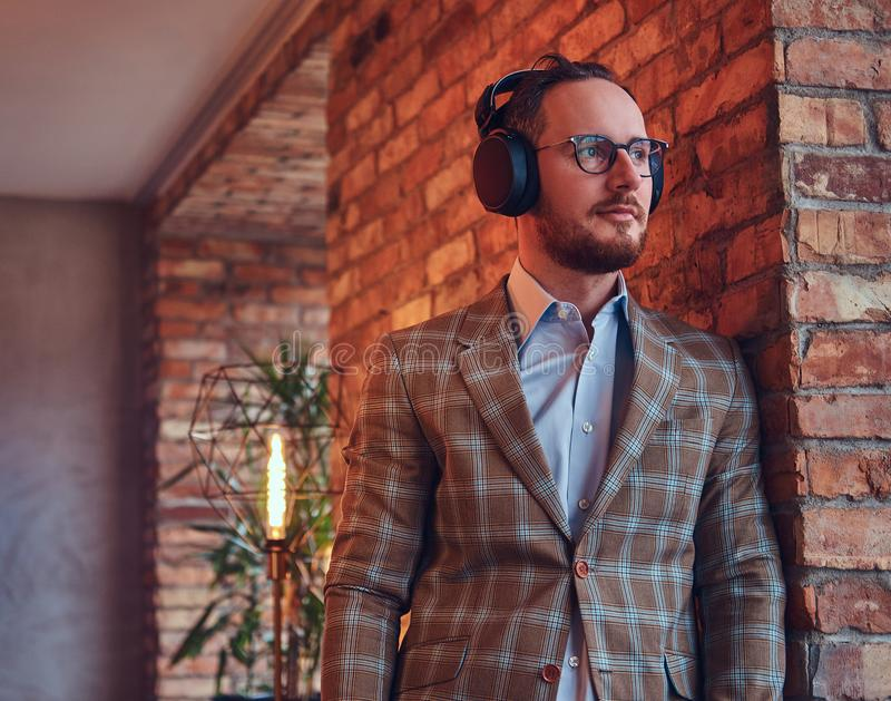 Portrait of a stylish man in a flannel suit and glasses listening music leaning against a brick wall in a room with loft stock images
