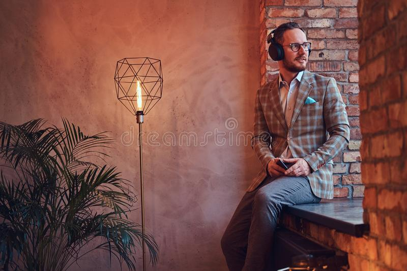 Portrait of a stylish man in a flannel suit and glasses listening music with the phone and headphones sitting on a stock photos