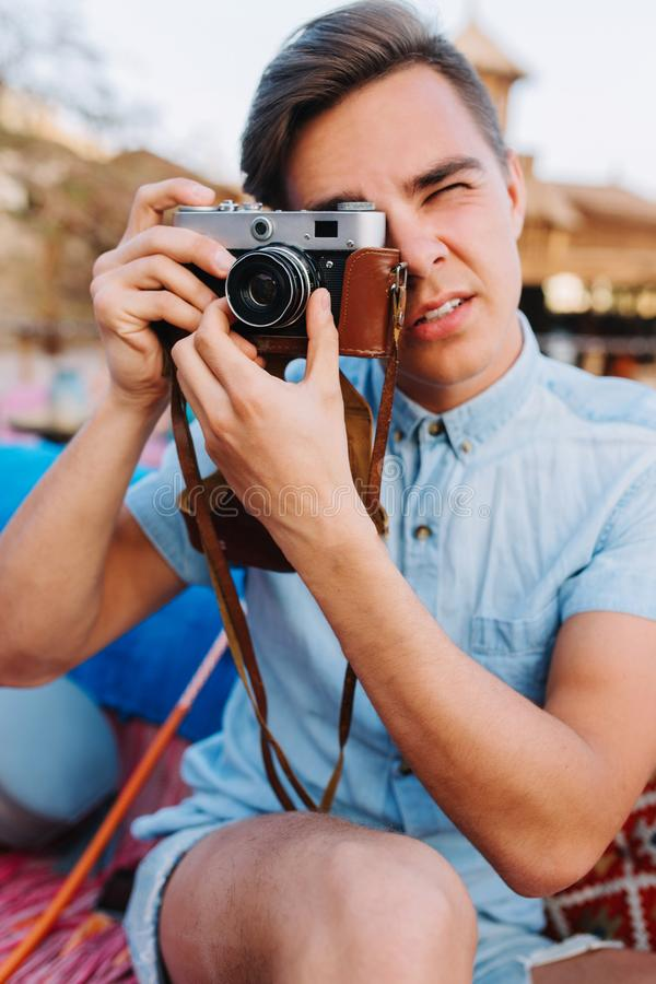 Portrait of stylish photographer in trendy light-blue denim shirt taking photo on blur background. Handsome young man royalty free stock images