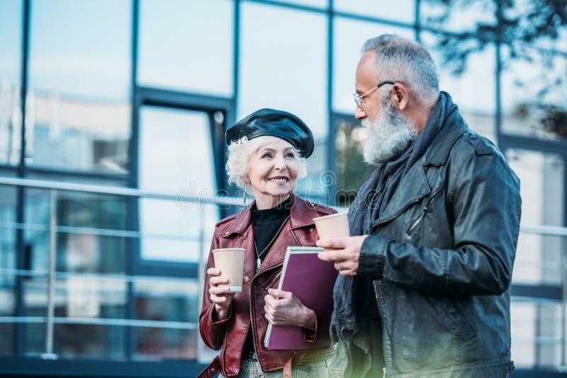 Portrait of stylish senior couple with coffee to go walking. On street stock photo
