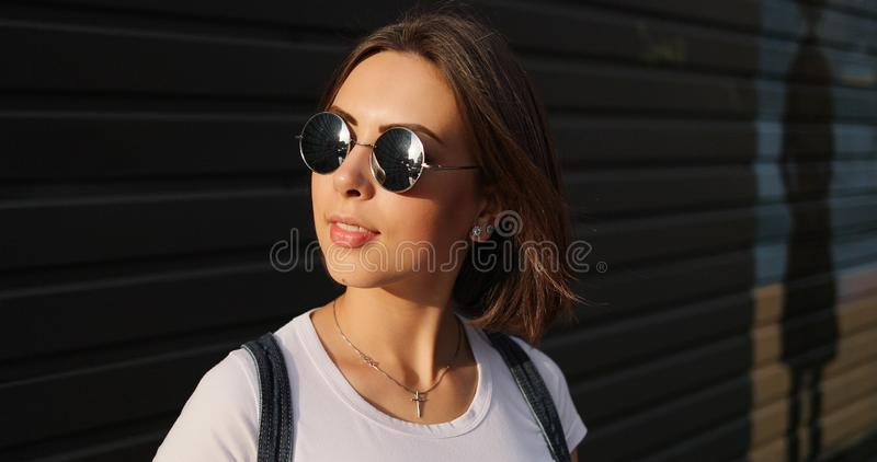 Portrait of stylish serious girl with glasses posing in city. royalty free stock images