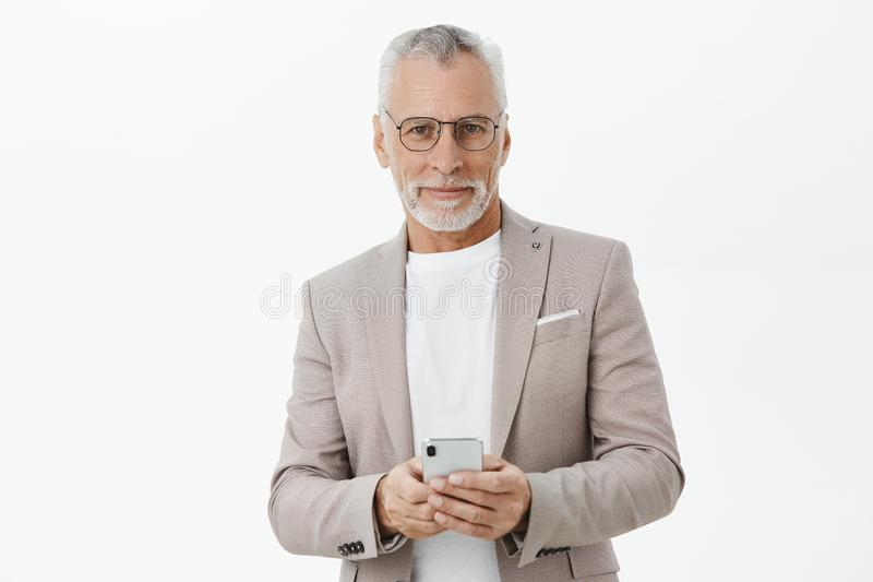 Portrait of stylish and smart confident senior businessman in glasses and elegant formal suit holding smartphone against. Chest smirking at camera pleased with royalty free stock image