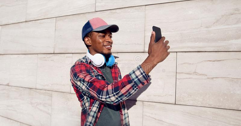 Portrait stylish smiling african man taking selfie picture by phone with headphones in baseball cap, plaid shirt on city street stock photos