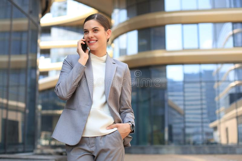 Portrait of stylish smiling business woman in fashionable clothes calling on mobile phone near office.  royalty free stock image