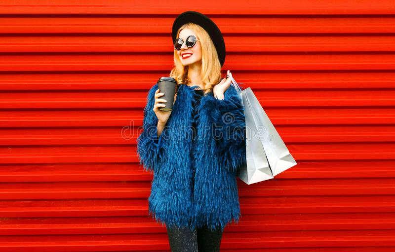 Portrait stylish smiling woman with coffee cup and shopping bags wearing blue faux fur coat, black round hat and sunglasses posing stock photography