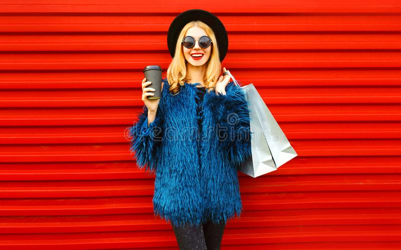 Portrait stylish smiling woman with coffee cup and shopping bags wearing blue faux fur coat, black round hat and sunglasses posing royalty free stock image