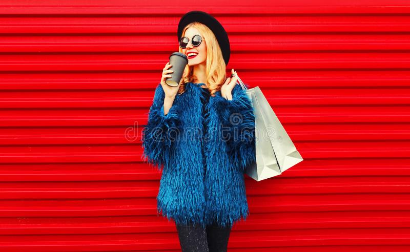 Portrait stylish smiling woman drinking coffee holding shopping bags wearing blue faux fur coat, black round hat and sunglasses royalty free stock photography