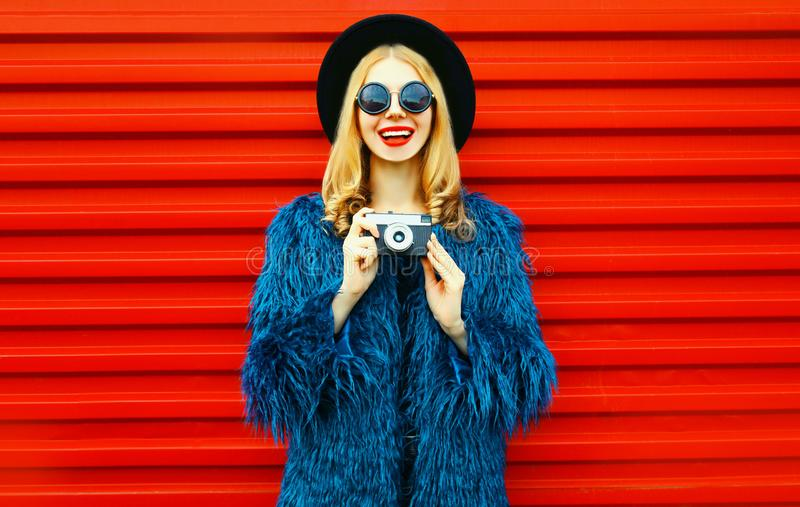 Portrait stylish smiling woman with retro camera wearing blue faux fur coat, round hat and sunglasses over red wall royalty free stock images