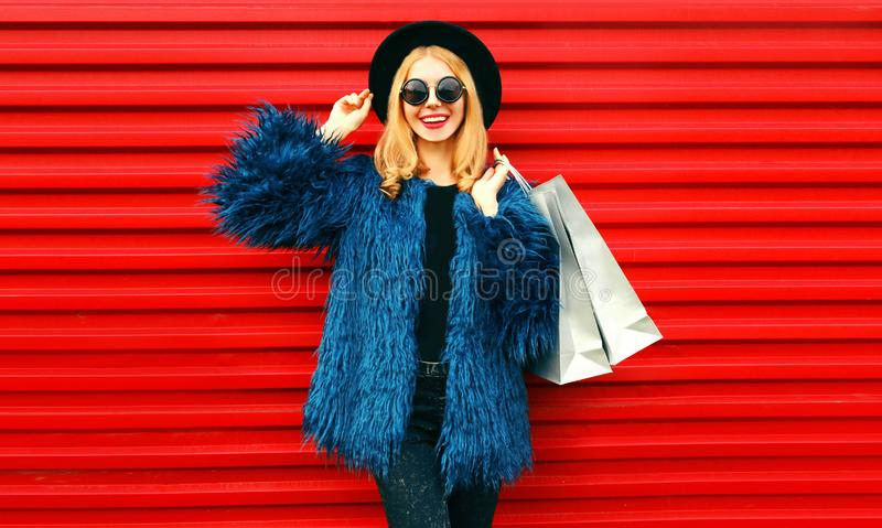 Portrait stylish smiling woman with shopping bags wearing blue faux fur coat, black round hat and sunglasses posing over red wall royalty free stock photo
