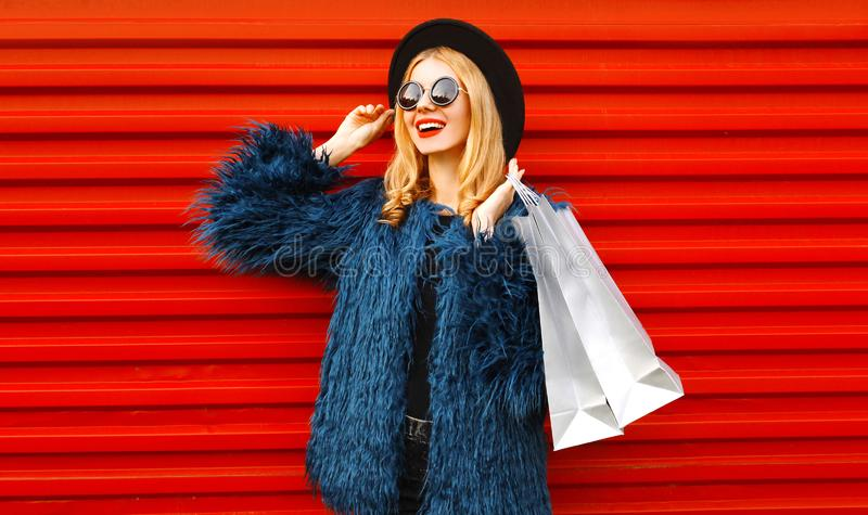 Portrait stylish smiling woman with shopping bags wearing blue faux fur coat, round hat and sunglasses posing and looking away stock photos