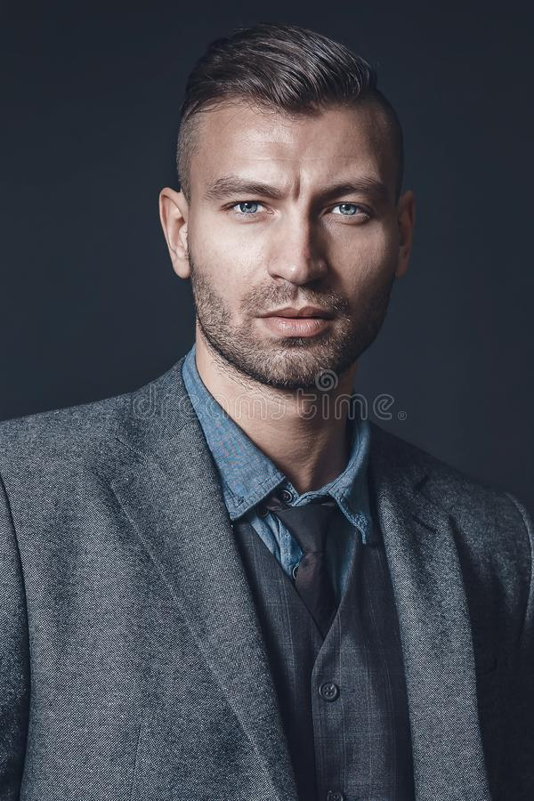 Portrait of stylish successful brutal man in gray suit with fashionable haircut on background of gray wall royalty free stock photos