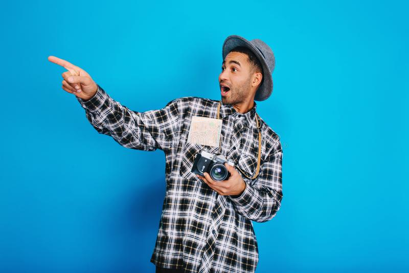 Portrait stylish surprised handsome guy with camera, map, in hat having fun on blue background. Travelling, enjoying royalty free stock images