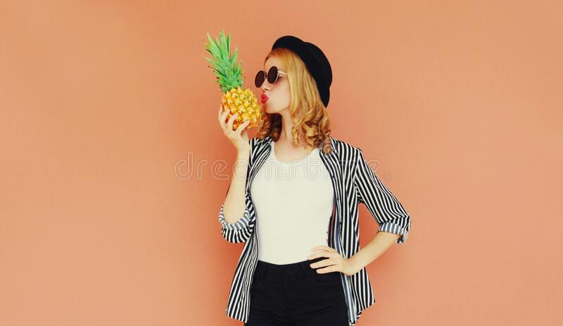 Portrait of stylish woman kissing pineapple wearing a black hat, sunglasses, striped shirt royalty free stock photos