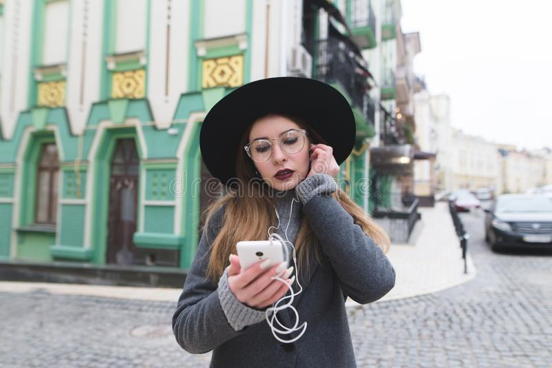 Portrait of a stylish woman listening to music in headphones on the backdrop of a beautiful old town. royalty free stock photography