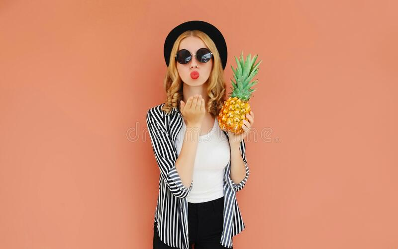 Portrait of stylish woman with pineapple blowing red lips sending sweet air kiss wearing a black hat, sunglasses, striped shirt stock images