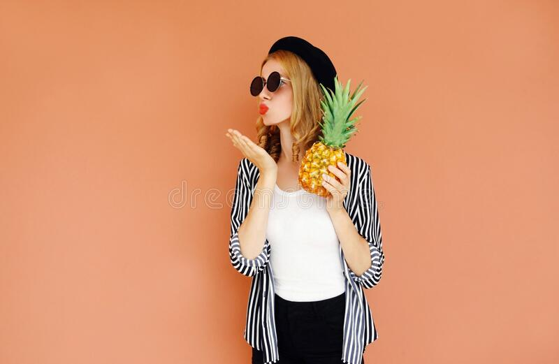 Portrait of stylish woman with pineapple blowing red lips sending sweet air kiss wearing a black hat, sunglasses, striped shirt royalty free stock image