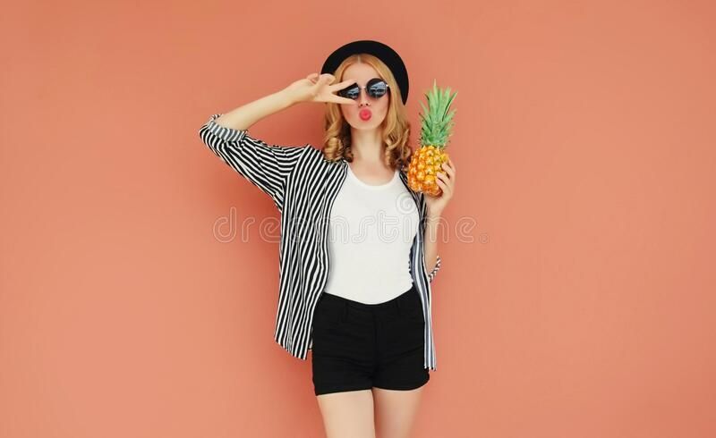 Portrait of stylish woman with pineapple blowing red lips sending sweet air kiss wearing a black hat, sunglasses, striped shirt royalty free stock images