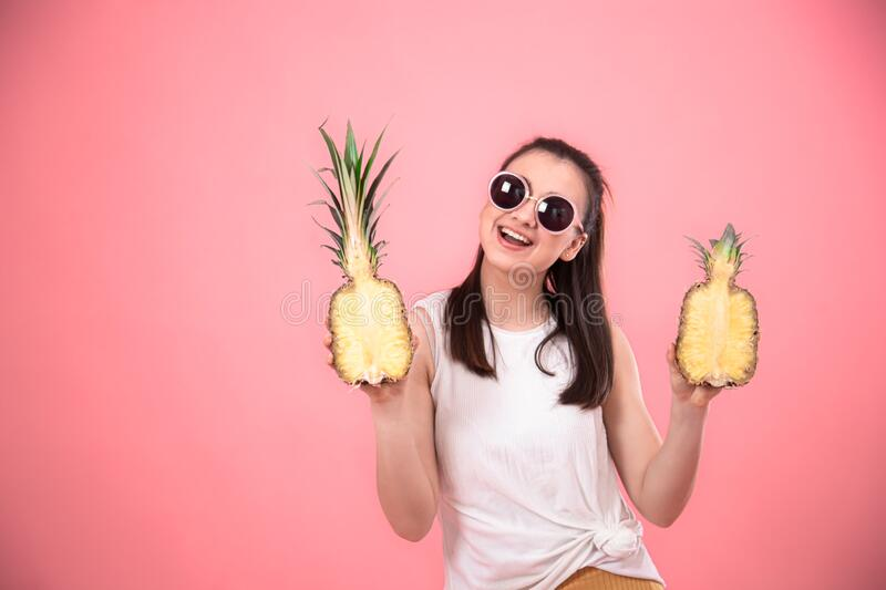 Portrait of a stylish woman on a pink background with pineapples in her hands. Summer concept royalty free stock photography