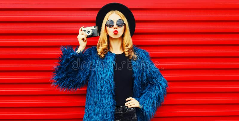 Portrait stylish woman with retro camera blowing red lips sending sweet air kiss wearing blue faux fur coat royalty free stock images