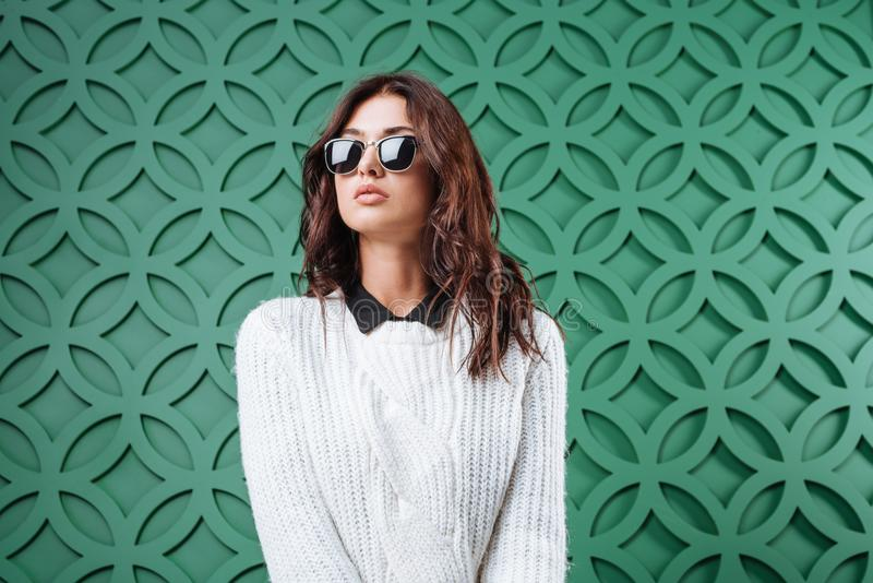 Portrait of stylish woman in white sweater and black sunglasses on green, stock photo