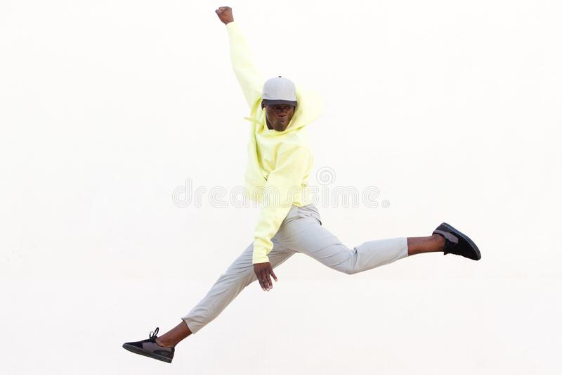 Stylish young African American man jumping and dancing on white background royalty free stock image