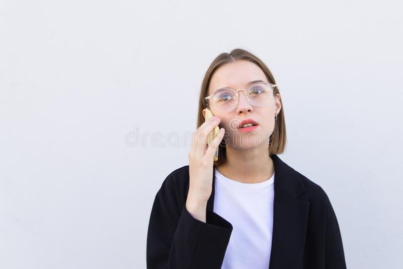 Portrait of a stylish young female office worker in glasses and a jacket, talking on a smartphone stock photos