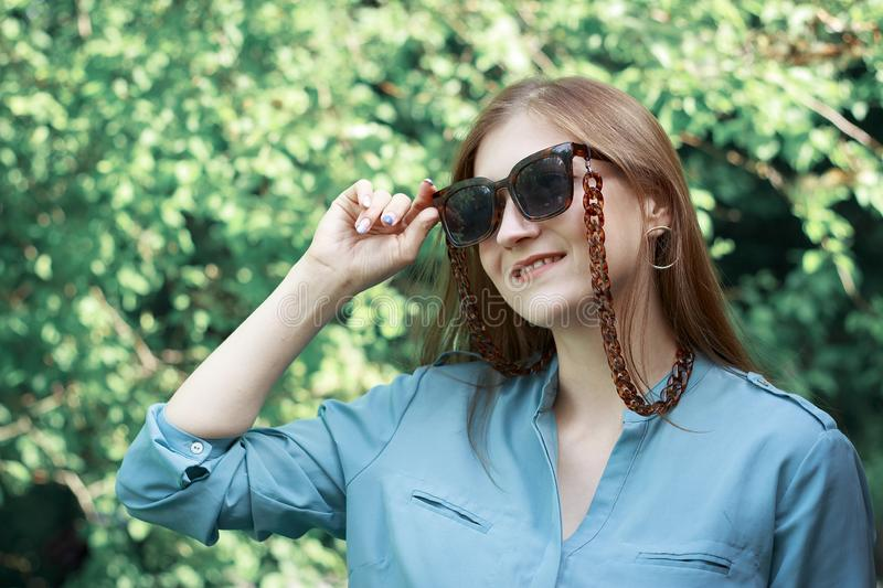 Portrait of a stylish young girl in sunglasses and with a bandage on her head, on the background of the stairs royalty free stock photo