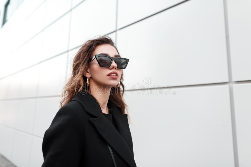 Portrait of a stylish young hipster woman in trendy glasses in a black coat with sexy lips with luxurious gold earrings stock photography