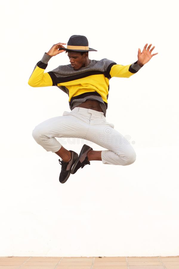 Stylish young male dancer jumping and showing his moves on white background. Portrait of stylish young male dancer jumping and showing his moves on white royalty free stock image