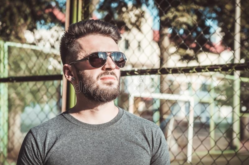 Portrait of a stylish young man with a beard and black glasses on the sports field, metal grille stock images