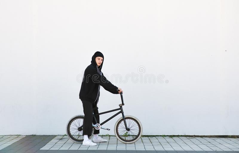 Portrait of a stylish young man with a bmx bike on the background of a white wall stock photography