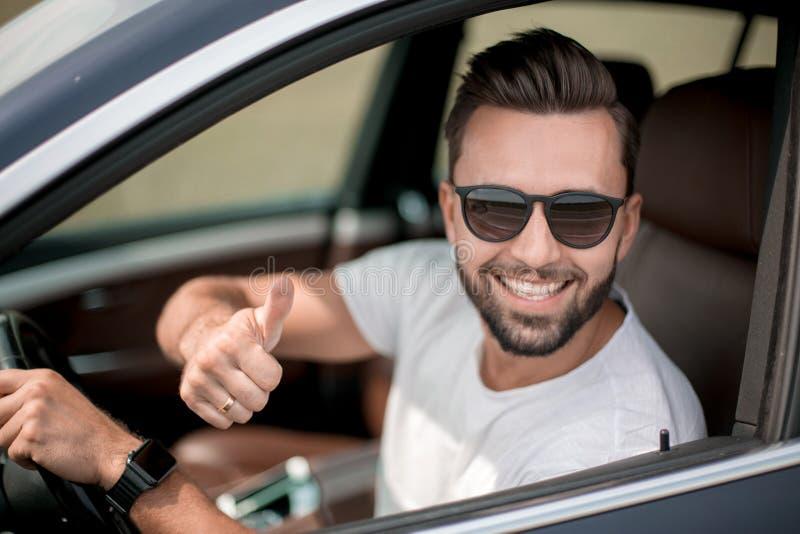 Stylish young man driving a convertible car royalty free stock photo