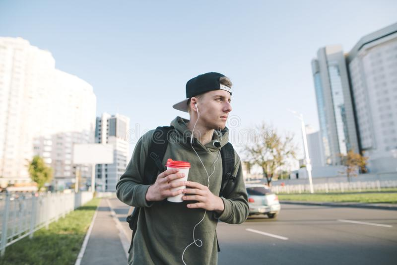 Portrait of a stylish young man walking down the street of his city with a cup of coffee in his hands and listening to music in th royalty free stock photography