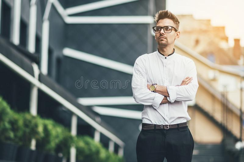 Portrait of stylish young man wears white shirt and wirstwatch on the street. Happy smiling man posing outdoor in the stock images